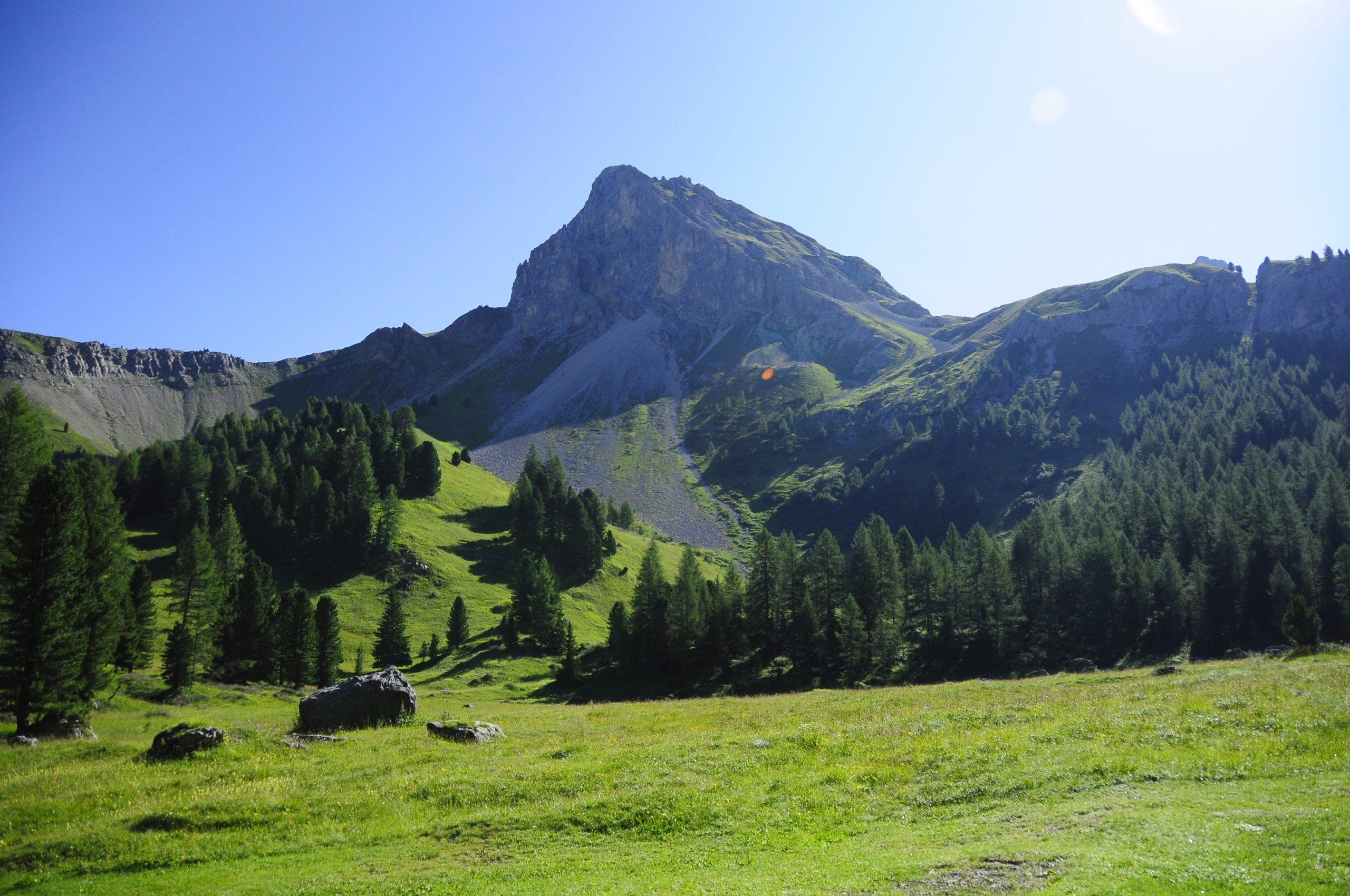 La roccia pura che contrasta con il cielo azzurro ed i prati verdeggianti
